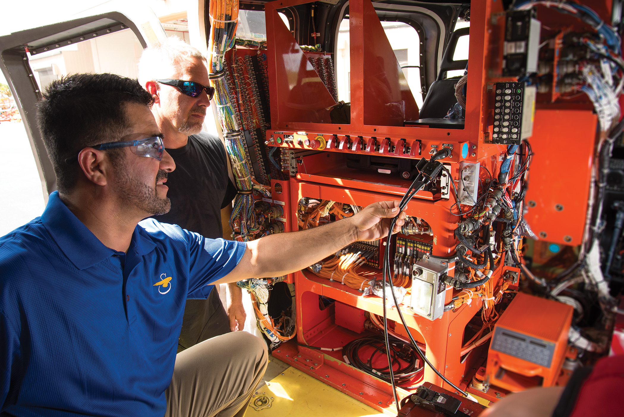 "Former Sikorsky intern and now an employee, PBSC graduate Edwin Carranza works inside the Sikorsky S-76D™ commercial helicopter as Terry Stein, crew chief, observes. ""One of the benefits of the internship was the kind of commitment that Sikorsky has to working with students,"" says Carranza."