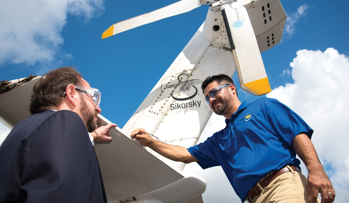 John Fischetti (right), general manager of Sikorsky's Development Flight Center and PBSC business partner, and Edwin Carranza, a Sikorsky instrumentation technician and graduate of PBSC's Electrical Power Technology A.S. degree program, examine the nine-passenger S-76D™ commercial helicopter.