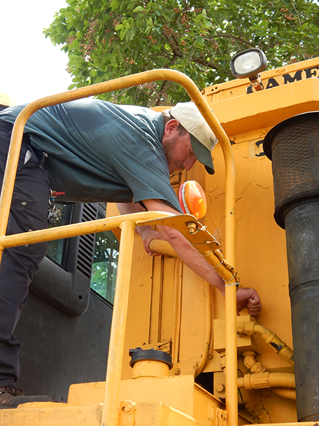 Carl (Trey) Dean, Belle Glade campus groundskeeper and a student in the Heavy Equipment Mechanics program, examines the harvester.