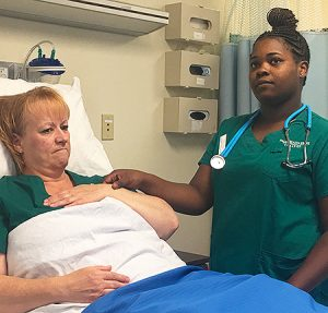 Students receive hands-on training in campus labs as well as at local clinical sites. In the lab, student Elizabeth King portrays the patient, while classmate Torkita Williams takes her pulse.
