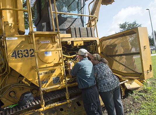 Heavy Equipment Mechanics students working on a harvester