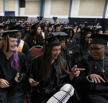 Spring graduates share a laugh. Click the image to view more pictures. Photos by Lindsay McGlynn